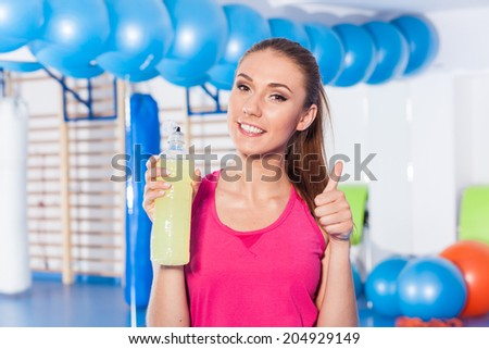Young girl drinking isotonic drink, gym. She is happy and full of positive emotion. Thumb up - stock photo
