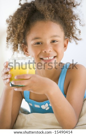Young girl drinking orange juice in living room smiling - stock photo