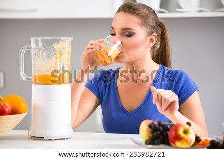 Young girl drinking tasty juice, healthy  fruits smoothies - stock photo