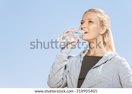 Young girl drinking water after morning run - stock photo