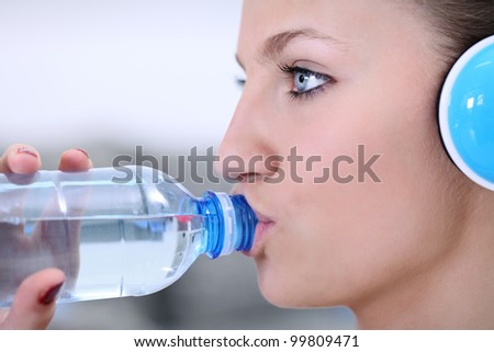 Young girl drinking water with headphones, side view
