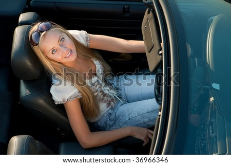young girl driving cabrio car, on sunset light - stock photo