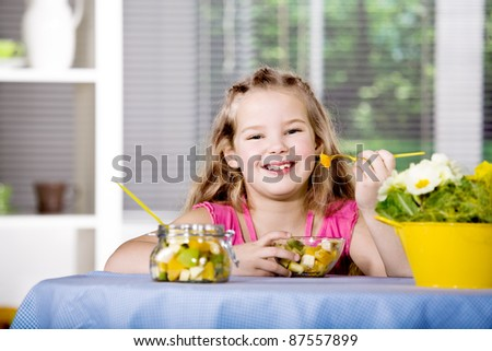 young girl eating a fruit salad at home. A studio shoot.