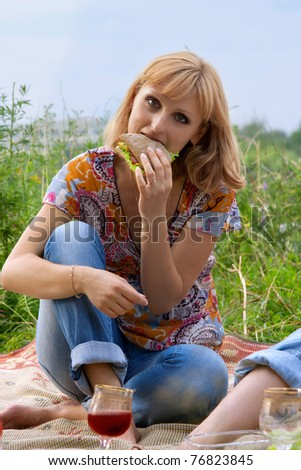 Young girl eating a sandwich at a picnic - stock photo