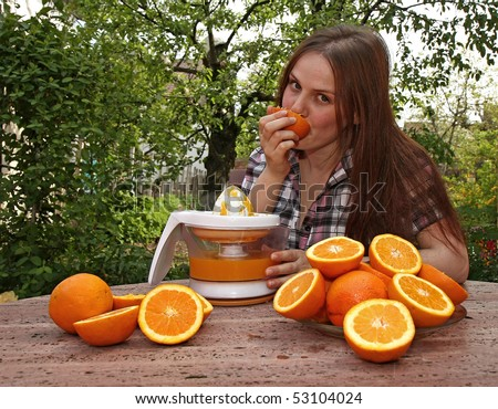 Young girl eating an orange while she make orange juice in the garden - stock photo