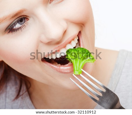 Young girl eating Brussels sprout - stock photo