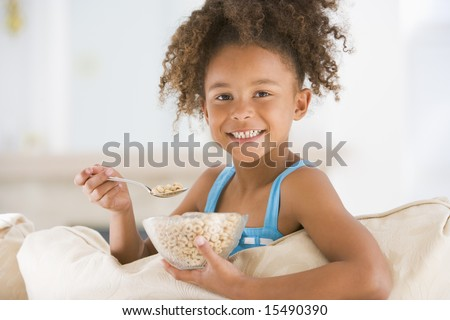 Young girl eating cereal in living room smiling - stock photo
