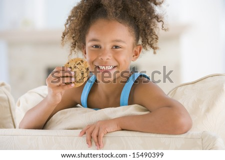 Young girl eating cookie in living room smiling - stock photo
