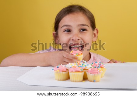 Young girl eating cupcakes with big brown eyes on a yellow background - stock photo