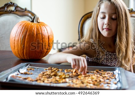 Young girl eating fresh baked pumpkin seeds