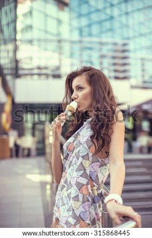 Young girl eating ice cream in the city street. - stock photo