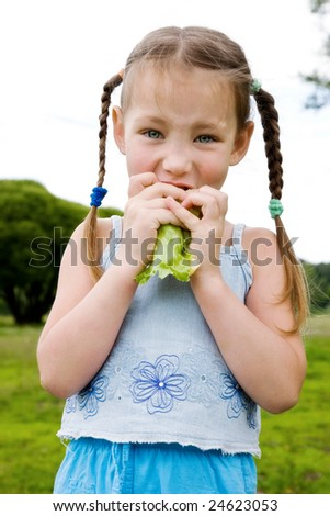 Young girl eating lettuce - stock photo
