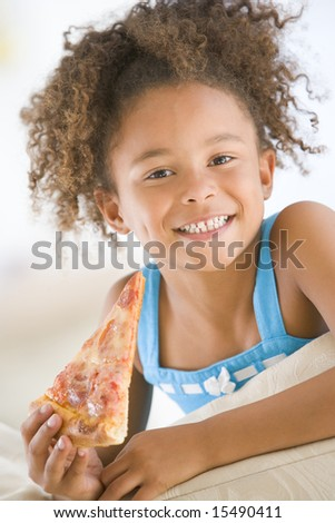 Young girl eating pizza slice in living room smiling - stock photo