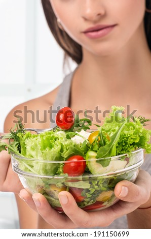 Young girl eating salad sitting on her bed at home - stock photo