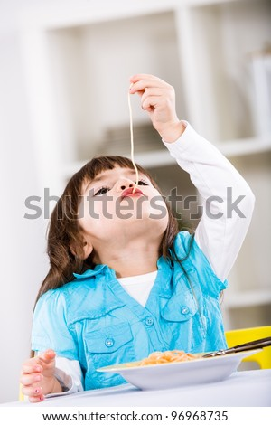 young girl eating spaghetti at home. A studio shoot.