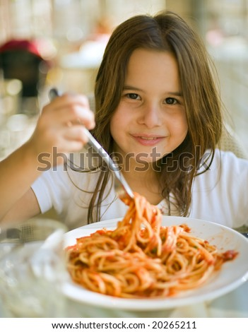 young girl eating spaghetti in restaurant - stock photo