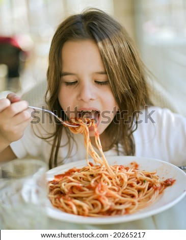 young girl eating spaghetti in restaurant