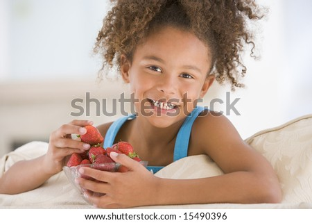 Young girl eating strawberries in living room smiling - stock photo
