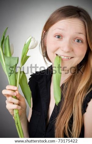 Young girl eating tulips - stock photo