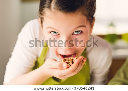 Young girl eating walnuts - healthy eating concept  - stock photo