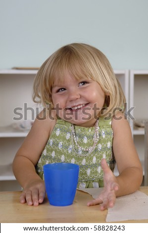Young girl eats her snack during the break at her preschool classes. - stock photo