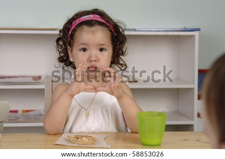 Young girl eats her snack during the break at her preschool classes.