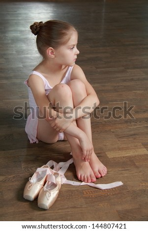 Young girl engaged in a pink ballet tutu and pointe in the ballet hall on the wooden dance floor - stock photo