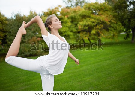 Young girl engaged in gymnastics in the park - stock photo