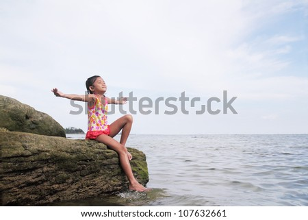 Young girl enjoying a peaceful day by the sea. - stock photo