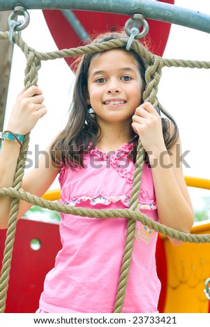Young girl enjoying climbing rope activity in outdoor park - stock photo