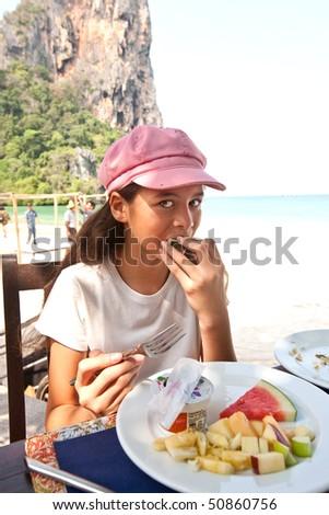 Young girl enjoying fresh fruit breakfast by the beach - stock photo