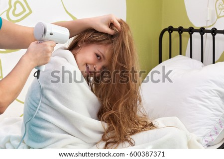 Young girl enjoying her hair being dried after bath - sitting on the bed and smiling