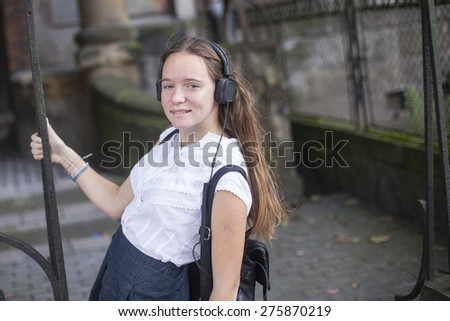 Young girl enjoying music in headphones on the street. - stock photo