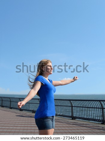 Young girl enjoying sun and wind by the ocean. - stock photo