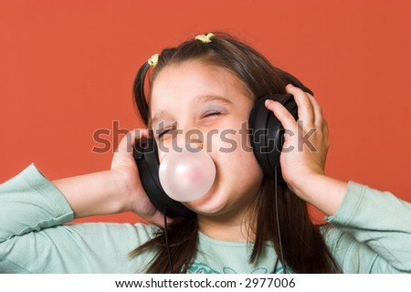Young girl enjoying the music and making a bubble from chewing gum - stock photo