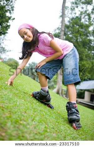 Young girl enjoying the outdoor park in her rollerblade - stock photo