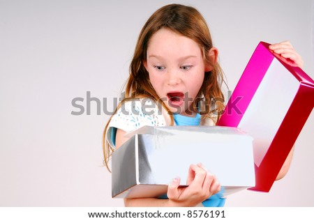 Young Girl Excited While Opening Gift - stock photo