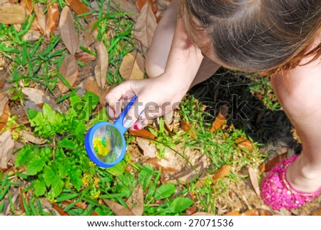 young girl exploring in yard using magnifying glass - stock photo