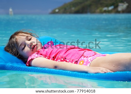 Young girl, eyes closed & covered in sand, floating peacefully in Magens Bay - stock photo