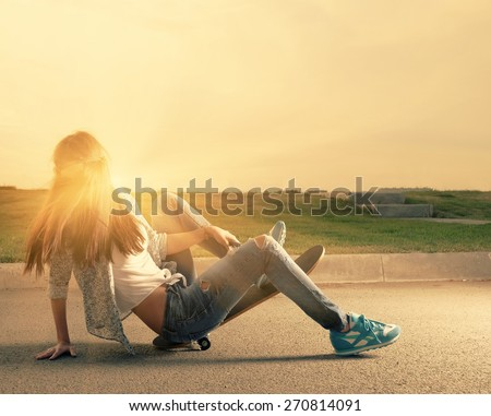 Young Girl Falling off Skateboard backlit by sunset. Copyspace. Image full of sunshine - stock photo