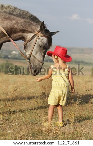 young girl feeding horse on natural background - stock photo