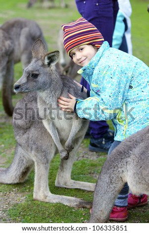 Young girl feeding kangaroos in Phillip Island Wildlife Park, Australia - stock photo