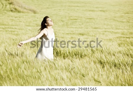 Young girl feeling freedom in field - stock photo