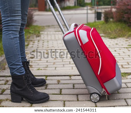 Young girl feet's in jeans with near a red travel suitcase. - stock photo