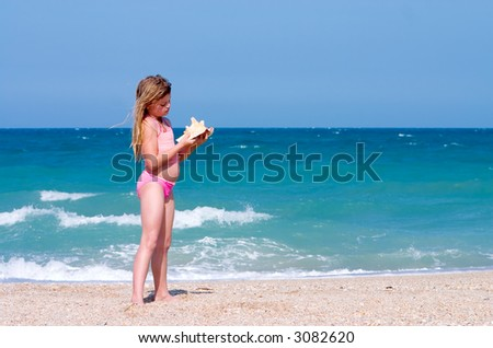 Young girl finds shell on beach. Atlantic Ocean, Florida east coast - stock photo