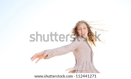 Young girl flicking her wet hair in the air, smiling against the sky. - stock photo