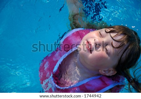 Young Girl floating in swimming pool - stock photo