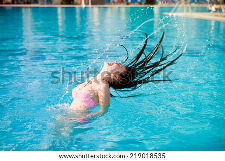 Young girl floating in the pool on a summer day