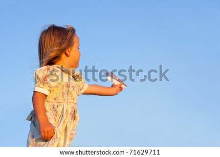 young girl  flying a paper airplane - stock photo