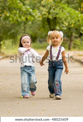 Young girl-friends go for a walk the park